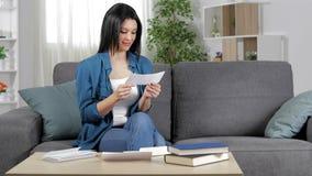 Mujer feliz que lee un recibo en casa almacen de video