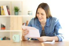 Mujer feliz que lee una letra en casa foto de archivo libre de regalías