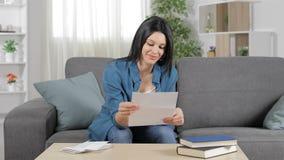 Mujer feliz que lee una letra en casa almacen de metraje de vídeo