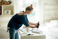 Mujer feliz que limpia su ordenador portátil Imagen de archivo
