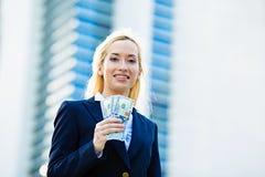 Mujer feliz que lleva a cabo billetes de dólar Imágenes de archivo libres de regalías