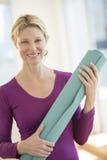 Mujer feliz que lleva a cabo el ejercicio Mat In Health Club Foto de archivo