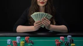 Mujer feliz que lleva a cabo el manojo de los dólares, sentándose en la tabla del casino, ganador del juego, éxito almacen de metraje de vídeo