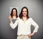Mujer feliz que lleva a cabo su imagen triste Imagenes de archivo