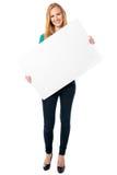 Mujer feliz que lleva a cabo a un tablero blanco en blanco Fotos de archivo libres de regalías