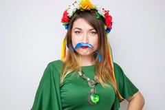 Mujer feliz que lleva en el vestido verde que juega con la cinta como bigote Mujer hermosa con la guirnalda de flores Imagen de archivo libre de regalías