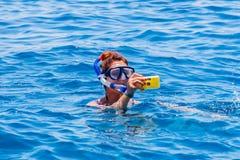 Mujer feliz que lleva una máscara en el mar, junto con una cámara Imágenes de archivo libres de regalías