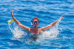 Mujer feliz que lleva una máscara en el mar, junto con una cámara Foto de archivo