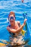 Mujer feliz que lleva una máscara en el mar, junto con una cámara Fotografía de archivo