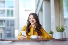 Mujer feliz que manda un SMS en smartphone en el café de la ciudad Imagen de archivo