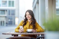 Mujer feliz que manda un SMS en smartphone en el café de la ciudad Fotos de archivo libres de regalías