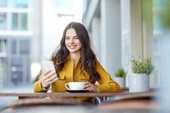 Mujer feliz que manda un SMS en smartphone en el café de la ciudad Fotos de archivo