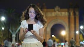 Mujer feliz que manda un SMS en smartphone en la noche en Barcelona almacen de video