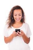 Mujer feliz que manda un SMS en su teléfono imagenes de archivo
