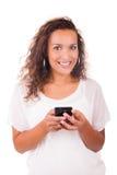 Mujer feliz que manda un SMS en su teléfono fotografía de archivo