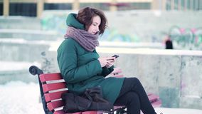 Mujer feliz que manda un SMS en un teléfono elegante mientras que se sienta en un banco en ciudad del invierno contra los bloques metrajes