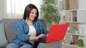 Mujer feliz que mecanografía en el ordenador portátil en casa