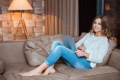 Mujer feliz que miente con el ordenador portátil en el sofá Imagenes de archivo