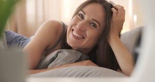 Mujer feliz que miente en cama en camisa de dormir almacen de video