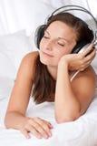 Mujer feliz que miente en el sofá blanco que escucha la música Foto de archivo
