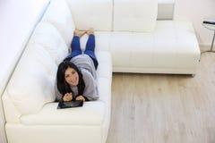 Mujer feliz que miente en el sofá que juega con la tableta Imagen de archivo