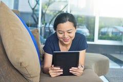 Mujer feliz que miente en el sofá y que usa el e-lector en casa Imagen de archivo