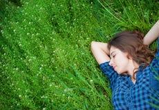 Mujer feliz que miente en la hierba y el sueño Imágenes de archivo libres de regalías