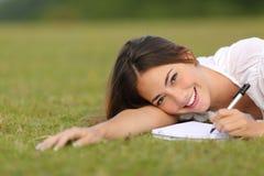 Mujer feliz que miente en la hierba y que escribe en un cuaderno Foto de archivo
