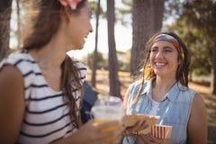Mujer feliz que mira al amigo mientras que se coloca en campo Imagen de archivo libre de regalías