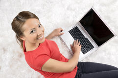 Mujer feliz que mira al revés con la computadora portátil Imagen de archivo
