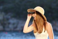 Mujer feliz que mira con los prismáticos en la playa Fotografía de archivo