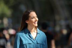 Mujer feliz que mira el lado en una calle de la ciudad Imagen de archivo