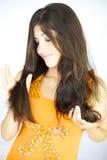 Mujer feliz que mira el pelo planchado satisfecho imagen de archivo