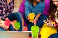 Mujer feliz que mira el teléfono móvil cerca de amigos Imagen de archivo