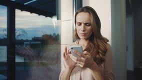 Mujer feliz que mira el teléfono móvil cerca Smartphone sonriente del movimiento en sentido vertical de la mujer almacen de metraje de vídeo