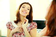 Mujer feliz que mira en su reflexión en el espejo Fotos de archivo