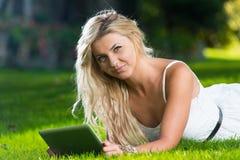 Mujer feliz que mira Ipad Imagen de archivo libre de regalías