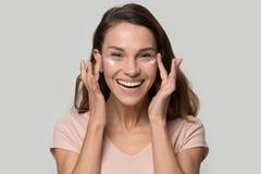 Mujer feliz que mira la cámara que aplica la crema hidratante del párpado fotografía de archivo