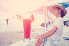 Mujer feliz que mira lejos cerca de la playa de la arena con el jugo fresco de la sandía Imágenes de archivo libres de regalías