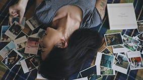 Mujer feliz que mira para recordar las memorias el jugar de las fotos metrajes