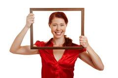 Mujer feliz que mira a través de marco Fotos de archivo
