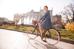 Mujer feliz que monta una bici cerca del teatro Imagenes de archivo