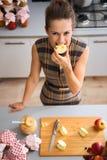 Mujer feliz que muerde en cuarto de la manzana en cocina Imagen de archivo