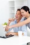 Mujer feliz que muestra algo en la computadora portátil Foto de archivo libre de regalías