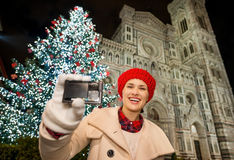 Mujer feliz que muestra la cámara de la foto cerca del árbol de navidad en Florencia Fotos de archivo
