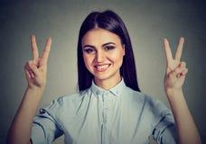 Mujer feliz que muestra la muestra de la mano de la paz de la victoria Fotografía de archivo