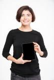 Mujer feliz que muestra la pantalla de tableta en blanco Imagenes de archivo