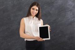 Mujer feliz que muestra la tableta digital en fondo gris Foto de archivo libre de regalías