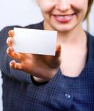 Mujer feliz que muestra la tarjeta de visita en blanco fotografía de archivo