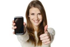 Mujer feliz que muestra su teléfono móvil y que gesticula el pulgar para arriba Fotografía de archivo libre de regalías
